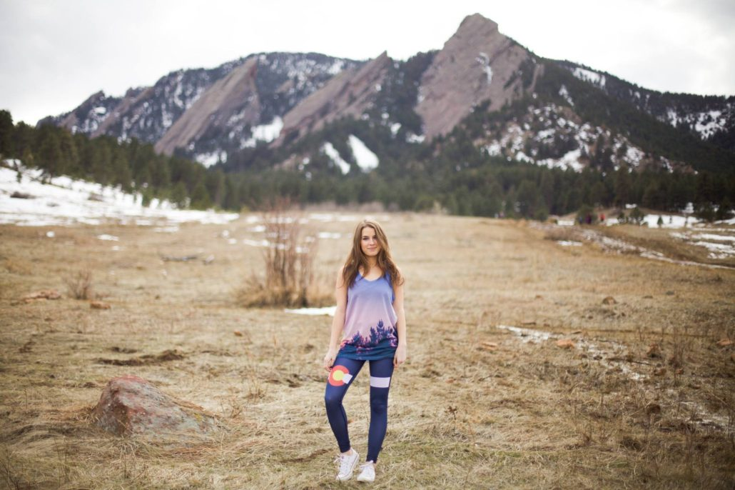 Girl in CO leggings in front of Flatirons